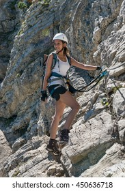 Smiling female hiker with white helmet, shorts, and other mountaineering safety equipment on rock face looking back