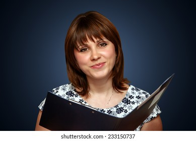 Smiling female holding book against the blue background
