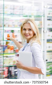 smiling female holding digital tablet and checking medications in drugstore