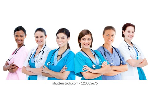 Smiling female hospital workers standing arms folded in line on white background