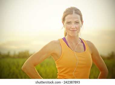 Smiling Female Jogger at Sunset (intentional sun glare)