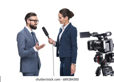 smiling female journalist with microphone and video camera interviewing businessman, isolated on white