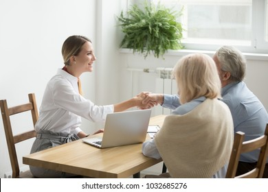 Smiling female lawyer, real estate agent or financial advisor handshaking older senior couple, insurance broker and aged family shake hands making purchase deal, investment or greeting at meeting