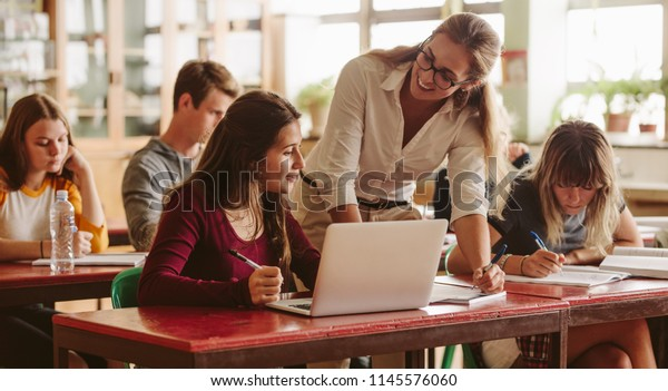 Smiling female lecturer helping student during her class. Student in a lecture with helpful teacher.