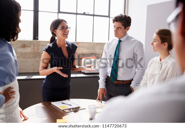 Smiling female manager in glasses addressing team in meeting