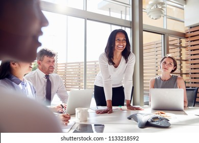 Smiling female manager listening to colleagues at a meeting