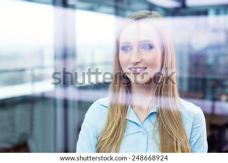 Smiling female manager standing in an office and looking through a window