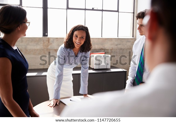 Smiling female manager and team standing in meeting room