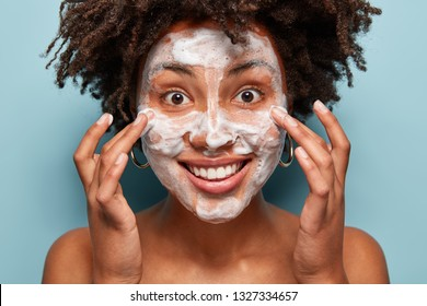 Smiling female massages face, washes with soap, demonstrates cleanliness or softness of skin, has curly haircut, models over blue background, has naked body, beautiful smile, bubble facial foam