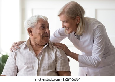 Smiling female middle-aged professional licensed practical nurse leaned toward to elderly man 80s clinic patient people having warm relations pleasant conversation, concept of caregiving care support