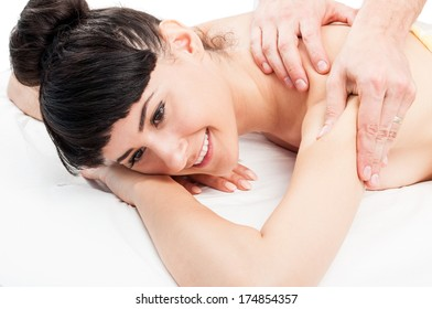 Smiling female model getting a relaxing massage from a male masseur.