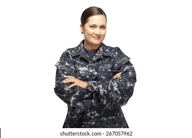 Smiling female in navy uniform with arms crossed posing against white background