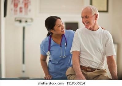 Lächelnde weibliche Krankenschwester trösten einen älteren männlichen Patienten in einem Prüfungsraum.