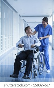 Smiling female nurse pushing and assisting patient in a wheelchair