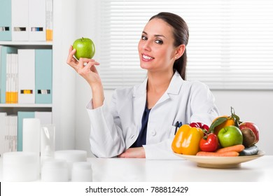 Smiling Female nutritionist holding a green apple and showing healthy vegetables and fruits in her office; Healthcare and diet concept