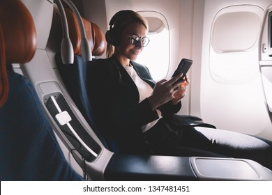 Smiling female passenger using smartphone connecting to wireless internet in airplane cabin, caucasian young woman traveler enjoying wifi hotspot service on board during travel time