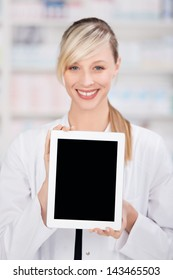 Smiling female pharmacist holding a digital tablet with an empty black display for copy-space