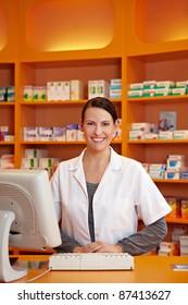 Smiling female pharmacist serving at counter in drugstore