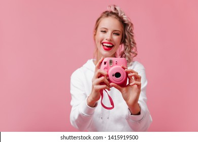 Smiling female photographer working on pink background. Good-humoured young lady with ponytail holding camera