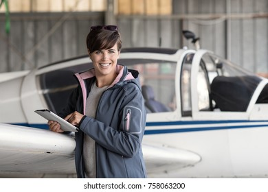 Smiling female pilot connecting with a digital tablet and using aviation apps, she is preparing for a flight, travel and aviation safety concept