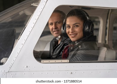Smiling Female Pilot and Flight Instructor Looking Through The Cockpit Window. Portrait of attractive young woman trainee pilot with headset. She is sitting next to instructor and looking at camera.