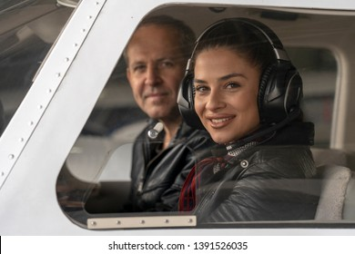 Smiling Female Pilot and Flight Instructor in an Aircraft Cockpit. Portrait of attractive young woman trainee pilot with headset. She is sitting next to instructor and looking at camera.