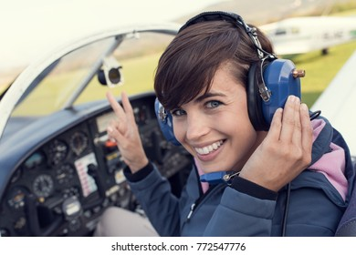 Smiling female pilot in the light aircraft cockpit, she is wearing aviator headset and making a V sign