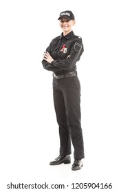 smiling female police officer with aids awareness red ribbon looking at camera with crossed arms isolated on white