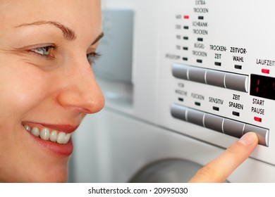 smiling female pressing a button on her washing machine