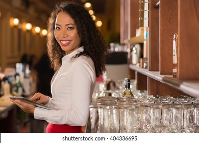 Smiling female pub owner with digital tablet looking at camera