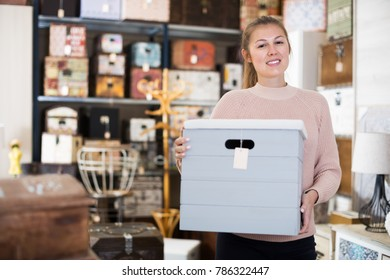 Smiling female purchaser choosing wooden box in furniture shop
