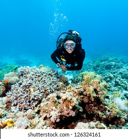 Smiling female scuba diver underwater on a coral reef