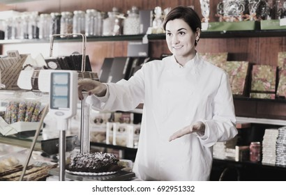 Smiling female seller weighing on scales festive chocolate cake in confectionery