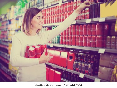 smiling female shopper searching for beer pack in supermarket