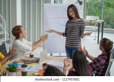 Smiling female  showing respect while team applauding congratulating appreciation and employee recognition concept