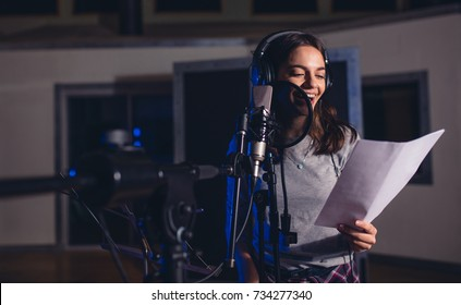 Smiling female singer with microphone and reading lyrics. Woman recording a song in music studio. Female playback singer recording her new album.