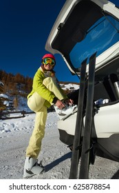 Smiling female skier putting her ski boots on