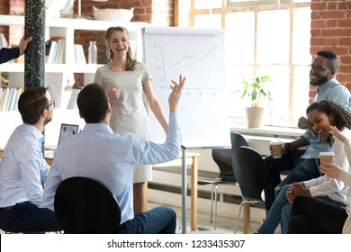 Smiling female speaker discussing business strategy with multiracial colleagues group, funny business coach laughing, making presentation on whiteboard, talking about results, explaining business plan