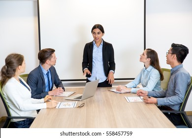 Smiling Female Speaker Giving Lecture to Audience