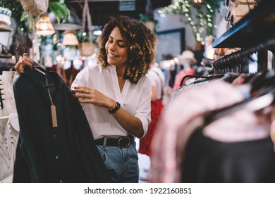 Smiling female standing near hangers with brand wear and laughing during Black Friday shopping with discounts, funny hipster girl enjoying pastime for update her wardrobe spending day in boutique