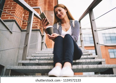 Smiling female student 20 years old watching new episode from serial via modern telephone while resting outdoors, happy hipster girl sitting at stairs enjoying coffee and messaging via mobile phone