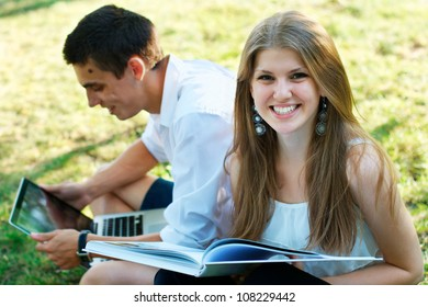 Smiling female student with a book with a young man at the background outdoors