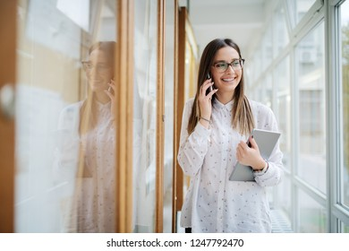 Smiling female student with eyeglasses and brown hair using smart phone and holding tablet while standing next to noticeboard.