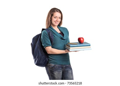 A smiling female student holding books and a red apple isolated on white background