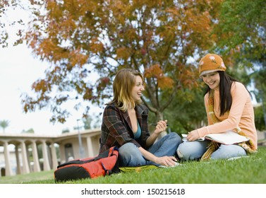 Smiling female students studying on college campus