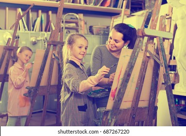 Smiling female teacher assisting student during painting class at art studio