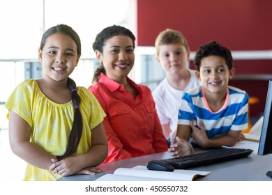 Smiling female teacher with children in computer room