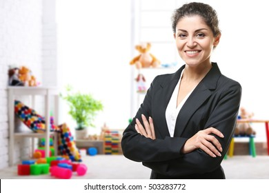 Smiling female teacher with clipboard on blurred playroom background