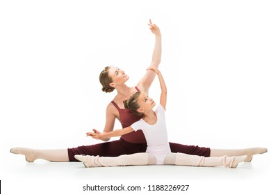 smiling female teacher showing exercise to little ballerina sitting on twine isolated on white background