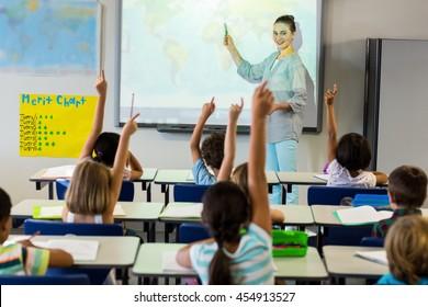 Smiling female teacher teaching schoolchildren using projector screen in classroom